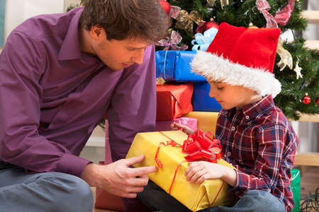 Father and son sitting and watching presents  under the christmas tree photo