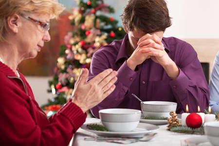 familia orando: Familia rezando en la mesa antes de la cena chritmas