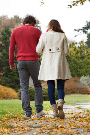 Young man and woman walking down autumn path photo