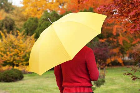 yellow umbrella: Man with yellow umbrella standing in park