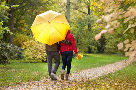 Young couple walking aroud the park under umbrella