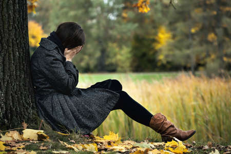 mujer llorando: Mujer joven que tiene la depresión de otoño y llorando Foto de archivo