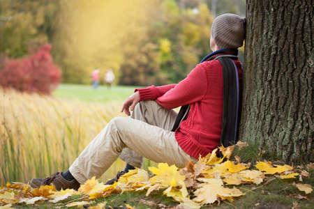 Sad man sitting under autumn tree in park photo