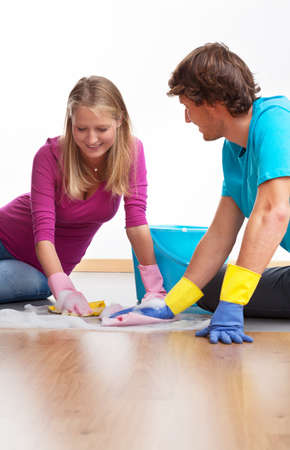 Young couple cleaning the floor and chatting photo