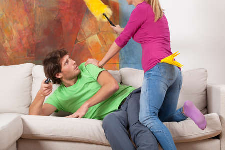 house wife: Woman trying to clean the hosue and man on a couch