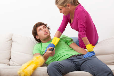 disturbing: Woman with cleaning duster disturbing her husband in watching tv