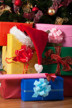 cloesup: Stack of gifts under the christmas tree with santas hat