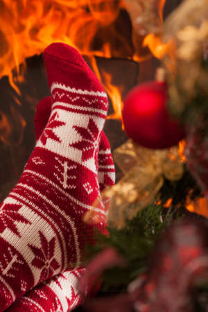 Somebody relaxing next to  fireplace and christmas tree, wearing a cute winter socks photo