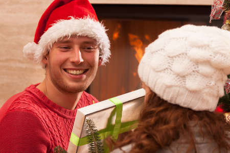 Brother and sister talking about christmas presents next to fireplace Stock Photo - 23875377