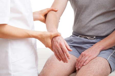 middle joint: Ortopedico esaminando il braccio ferito di uomo di mezza et�