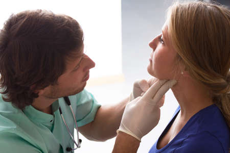 doctor examining woman: GP examining young woman, who has problems with throat