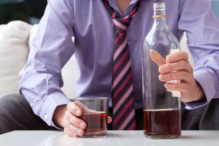 alcohol abuse: Man sitting on a couch with glass and bottle of whiskey