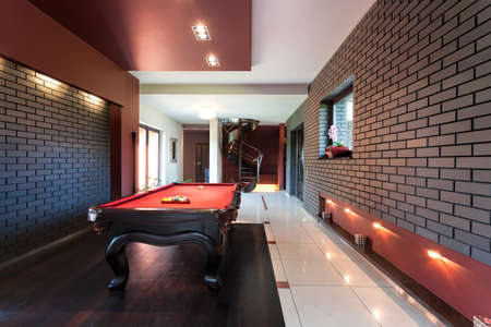 billiards room: Snooker table in a luxury interior with brick walls