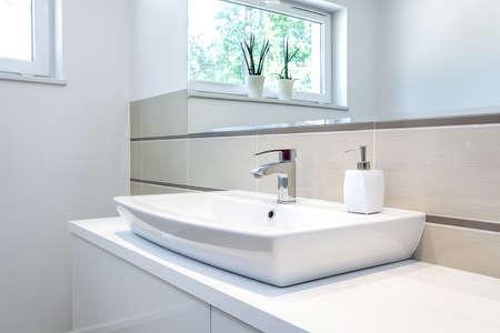 Lichte ruimte - een zilveren kraan in een witte badkamer Stockfoto