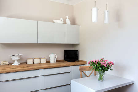 modern living room: Bright space - a white and elegant kitchen corner