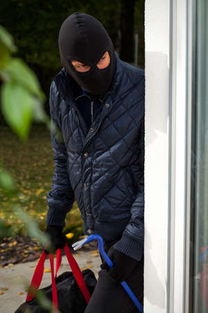 Burglar wearing mask with crowbar and bag photo