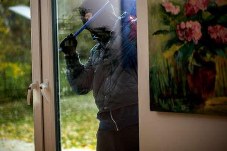 Inbreker probeert om het venster met koevoet te openen Stockfoto