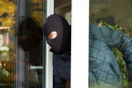 Housebreaker wearing a mask loking through the window photo