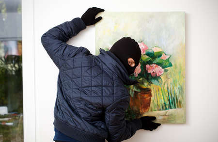 looting: Thief stealing the piece of art from gallery of art