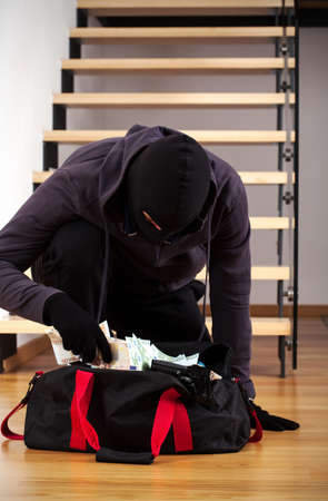safe house: Thief packing the stolen money to his bag Stock Photo