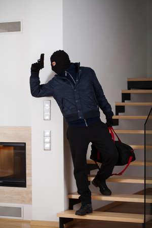 housebreaking: Burglar with a gun running away with loot Stock Photo