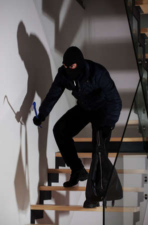 Burglar with a crowbar and bag creeping on stairs