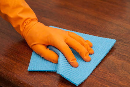 disinfect: A man with a glove polishing a woodentable with a rag