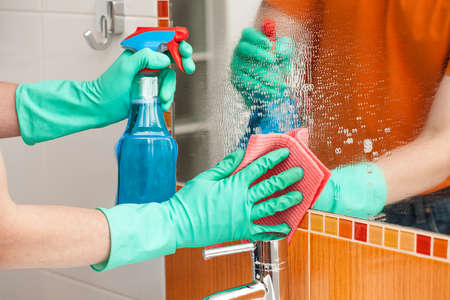 A man cleaning a mirror with a rag and a spray cleaner Stock Photo - 24026265