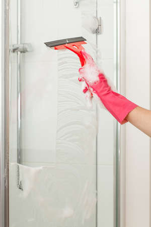 A man cleaning a shower glass  Stock Photo