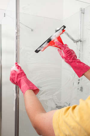 man shower: A man tiding up his bathroom with gloves using a cleaner Stock Photo