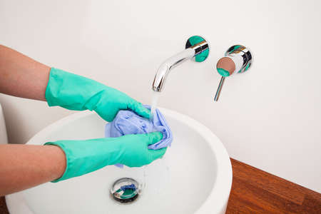 A man with gloves wetting a blue rag Stock Photo - 24026271