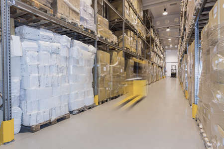 elevator operator: Yellow forklift moving in huge spacious warehouse Stock Photo