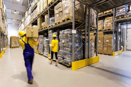 Warehouse worker with box and manager controlling products Imagens