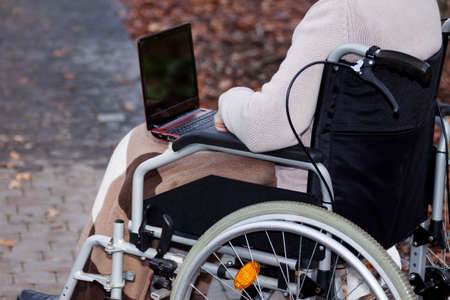 Disabled person using laptop and surfing the Internet photo