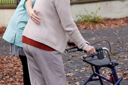 Verpleegster helpt oudere persoon om te lopen met rollator Stockfoto
