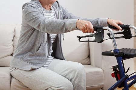 ancianos caminando: Disabled persona mayor de pie y sosteniendo en andador