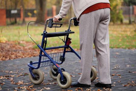 Gehandicapte oudere persoon lopen met rollator Stockfoto