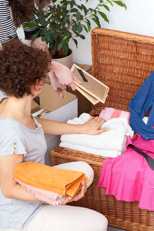 Woman arranging different things in wicker chest photo