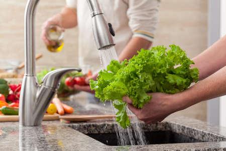 lavare le mani: Lavare le verdure fresche per una insalata con olio vivo