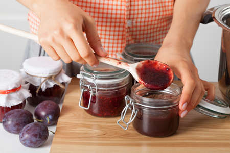 Woman tasting homemade marmalade with plums Stock Photo