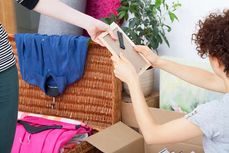 Young woman giving things to packing to other person photo
