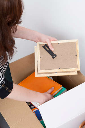 Woman packing photo frames into white box photo