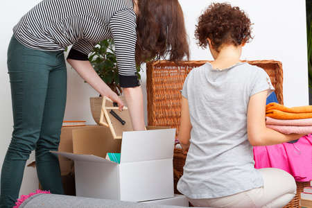 apartment cleaning: Two women packing things and clothes in their flat Stock Photo