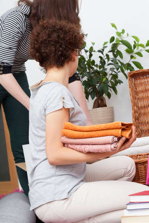 Woman with curly hair putting towels to the chest photo