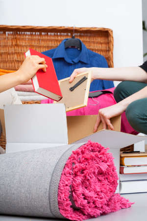 stuff: A closeup of packing books into a cardboard and a pink carpet Stock Photo