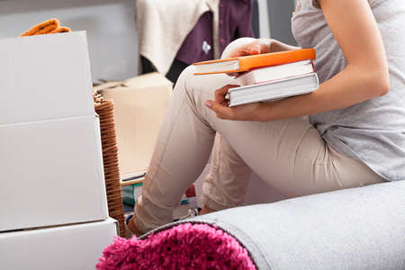 Woman sitting on rolled carpet during packing photo