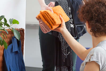 Woman passing colorful towels during packing stuff photo