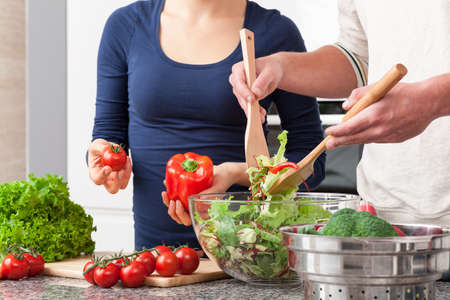 Couple cooperating in kitchen during making salad Imagens