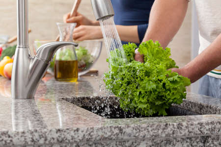 Washing a fresh lettuce for salad in sink , in the kitchen photo