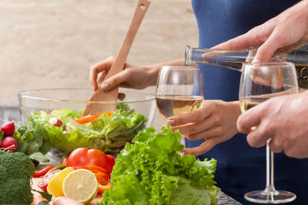 Couple preparing together a romantic dinner and drinking wine photo